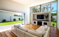 Open plan living area with TV and Fireplace feature wall. Glass sliding doors. High ceiling. Glass Windows and Walls. Floor boards. Lounge. G.J. Gardner Homes Australia.