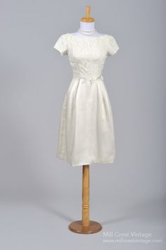 Designed in the 60's, this adorable cocktail vintage wedding dress is done in a silk satin and lace over an acetate lining in the bodice and a silk and cotton blend lining in the skirt. The bodice, do