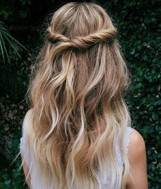 Twisted half-up half-down hairstyle with loose waves for a bohemian and romantic beauty look