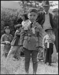 WW2 ¥ (1942) U.S.A. Centerville, California. This youngster is awaiting an evacuation bus. Evacuees of Japanese ancestry will be housed in War Relocation Authority centers for the duration. // Dorothea Lange, 9 May 1942