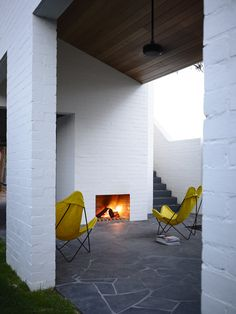 Outdoor fireplace: painted white brick walls, wood-panelled ceiling, slate grey pavers, yellow butterfly chairs