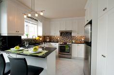 L'îlot et les armoires de style shaker de la cuisine ont été réalisés en polyester. Le tout est harmonisé avec un comptoir en granit noir cambrien.