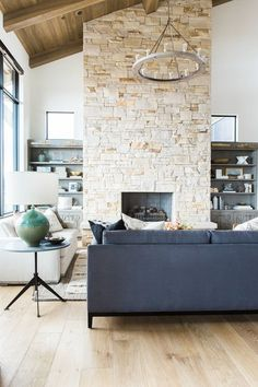 Great room with dramatic stone fireplace, layered rugs, and neutral color scheme