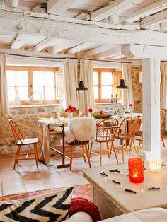 décoration maison de campagne - salle à manger accueillante avec déco murale en pierre de parement, aménagée avec une table rectangulaire, chaises orange et suspensions métalliques