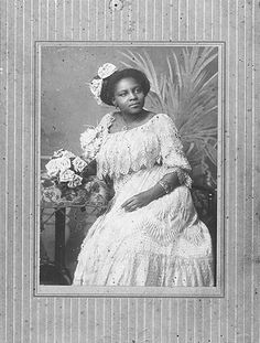 Seated woman, wearing a party dress and corsage, holding a bunch of artificial flowers.  Creator: E. W. Jackson 1900. Women in the Gilded Age.