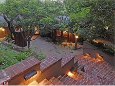 """Lighted Brick Terrance  of a Mid-Centrury Home the Hollywood Hills mansion that once belonged to Heath Ledger (and before that, Ellen Degeneres) was built in 1951 and has perks such as an outdoor movie lounge and """"multiple seating areas perched in the trees."""" The two-bedrooms, two-bathroom, 1,800-square-foot """"Treehouse,"""" as it's known, is now asking $2.795M."""