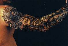 A steampunk tattoo design that creates the illusion that the guys arm is made of mechanical parts