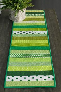 Today we're sharing a quick & easy quilted table runner! Here's an idea to use some of your favorite green fabrics for your St. Patrick's day table. We're going to play with green fat quarters from your stash – you'll need about about 10 to 20 for a 50″ runner. For color inspiration, think about…
