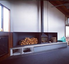 Warwick Mihaly farmer house living room. Radiante 800 on raised hearth with practical wood storage.
