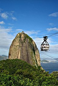 View of a peak situated near to the sea. A glass-paneled cable car passes suspended by cables.