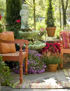 Chairs next to fountain and pot plants on patio ~ love all the flowers!