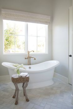 Beautiful white modern farmhouse bathroom with freestanding tub and herringbone tile floor - Jaimee Rose Interiors.