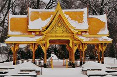The Thai Pavilion at Olbrich Gardens covered with snow. Photograph by Peter Patau.The pavilion features gold leaf etchings, a lacquer finish, and intricate decoration. Amazingly, the pavilion is able to withstand the winter weather of Wisconsin with no protection because it is constructed of plantation-grown teak and weather-resistant ceramic roof tiles. The gold leaf, however, is delicate and not able to withstand the oils of the human hand.