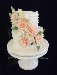 Textured fondant wedding cake with custom sugar flowers.