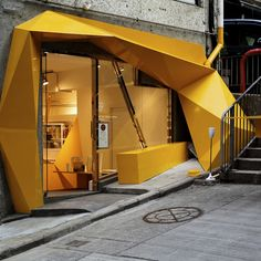 Its asymmetrical façade is like the result of a pixel explosion, garishly yellow, unwieldy but elegant - it's both graceless and graceful in equal measures...