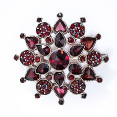 Bohemian Garnet Starbust Brooch in 9 Karat Gold. This extra-lovely central-European garnet brooch, crafted in 9 karat rose gold, is composed in three distinct layers of darkly glistening almandine garnets, including six heart shapes alternating with round pave' sections. Circa 1890, 1 1/4 inches diameter.