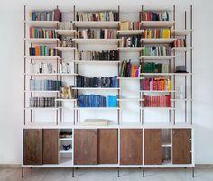 La libreria Ruggine è realizzata in musltristrato di betulla e ferro ossidato. Ha porte scorrevoli per l'apertura della consolle bassa