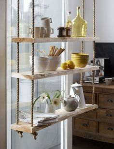 Eiken touwladder, houten stellingkast voor in diepe raam kozijn links in keuken. Oud emaille er op.