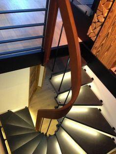 Escalier sur mesure suspendu deux quart tournant, cuir et béton, avec éclairage intégré aux marches et à la main courante.