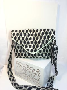 Our Newest Style Bag for this Season!! This Updated Messenger Bag has a fold-over main zippered body with an exterior pocket on each side. One pocket has a 9 zipper, the other pocket is designed for ease of access for your cell phone or other items.  This particular fabric is a lovely weight rayon blend decorator fabric in a black and white geometric design.  The bag is fully lined in a coordinating black and cream floral cotton fabric. The 1/1/2 wide strap is made with the same fab...