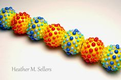 """""""Technicolor"""" by Heather Sellers. A lovely set of lampwork glass beads featuring monochromatic dots, strung in a rainbow pattern. ASGB dot themed bead exchange for June 2014. Join us on June 22nd at the Mesa Arts Center."""