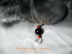 Necklace with an ancient wire wrapped swirl by BarbedWireJewelry