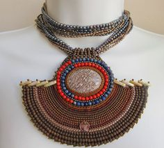 Crown Rose Gems, a collaborative workshop by Rosita nad Bernie Pisarchick. ZUMA  large Rhyolite Pendant necklace. Browns, reds and blues. Orbicular Rhyolite, Lapis Lazuli, Coral, Hematite and Pearls  31 inch length. $ 475.00 via Etsy