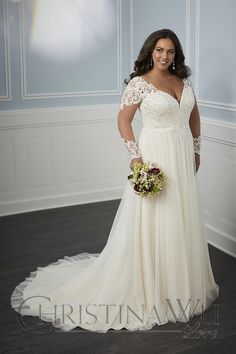 This Christina Wu Love 29345 A-line plus size bridal dress features a deep V-neckline, with illusion long sleeves that blend into the partial illusion back. The gathered skirt is made of layers of soft net and extends in a chapel train.