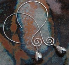 Hammered and tumbled sterling silver swirly hoops with a sterling silver bead dangle. $26.00