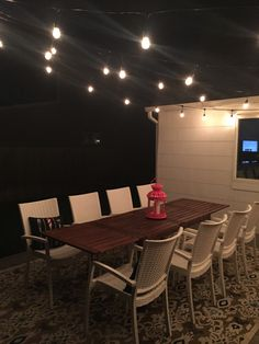 Outdoor dinging set up with string lights.