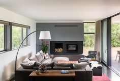Modern open concept living room in Boulder with a fireplace, gray and white walls, wood floors. Large slider opens to backyard.