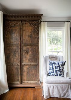 An antique cedar armoire stands in a corner of the living room | domino.com
