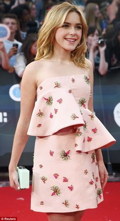 Mad Men actress Kiernan Shipka in a pale pink frock featuring an unusual asymmetric peplum-style adornment on the torso and two-tone pink and green jewelled embellishments all over.
