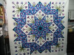 Radiant Lone Star quilts by Sheila Monnette -- This quilt is machine pieced and has paper pieced flowers. It is machine quilted. It has 36 different colors in the star points.