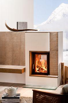 Das perfekte Panorama für den perfekten Kachelofen. Als Raumteiler mit Sitzbank ist er sowohl ein optischer Blickfang, als auch ein Möbelstück, das an kalten Wintertagen wunderbar wärmt.