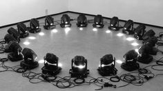 A kinetic installation. An array of moving heads displayed in a geometric configuration, a circle in this case, is programmed to deliver a choreography. The light shutter is opened with parsimony as the focus is put on the movements and the sounds of the motors: central are the moving heads themselves rather than the light patterns produced.  Instead of hidden in the scene in this situation the moving heads become the protagonists. For this first prototype twenty smaller moving heads were...