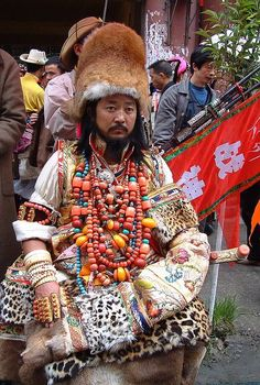 tibetan man wears all of his family jewelry for traditional festival. traditional Tibetan costume