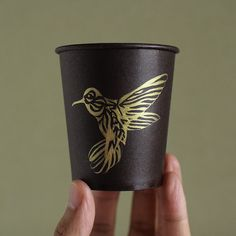 A hummingbird painted on a paper cup. #illustration #drawing #sketch #design #artcraft #art #papercup #hummingbird #gold #gouache