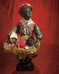 "All-Original French Musical Automaton ""Flower-Seller with Surprises"" by Gustav Vichy    25"" (64 cm.) A beautiful black-complexioned papier-mache lady with brown glass eyes,mohair lashes,painted brows,open mouth with two rows of teeth,dark mohair wig arranged under turban,carton torso and legs with bare feet,defined toes,wire upper arms,papier-mache hands,wearing her original elaborate silk and brocade costume"