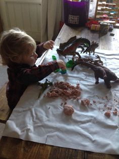 Dinosaurs - green play dough, packing material snow, a small tub of water, pebbles and moon sand. Later on L added a tube as a tree and I put some wooden beads in which she made into dino eggs.