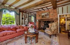 An impressive double aspect #drawingroom displaying heavy oak chamfered #beams, an #inglenook fireplace with wood burning stove and a bay window with French doors leading to the gardens. In Stoke by Clare, Sudbury, Suffolk