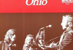 """Red banner with white word """"Ohio"""" with Crosby, Stills, Nash & Young playing on stage beneath"""