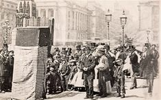 "A Punch and Judy show in Waterloo Place, with the Crimean War memorial in the background. Such raucous street entertainment was often disapproved of by authorities, but Dickens once defended it as a relief ""from the realities of life which would lose its hold upon the people if it were made moral and instructive""."