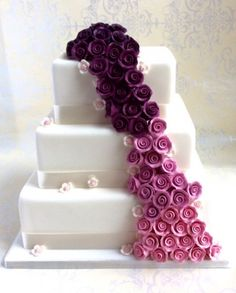 3 tier wedding cake. Fantastic Day. 3 tiers of shaded sugar roses tumble down the front of this square cake and little blossoms are scattered around like fallen confetti on a magical wedding day.