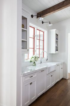 white kitchen rustic beam, pop of color in window panes