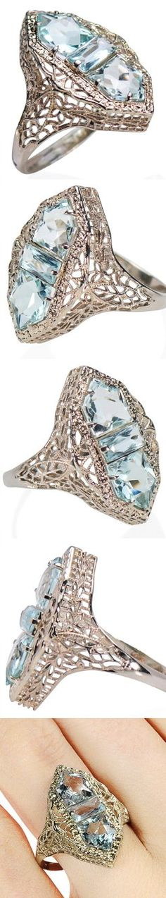 Aquamarine Dreams in a Vintage Filigree Ring, circa 1930. Delicate appearing lace-like renderings of wispy webs of 14k white gold form open work foliate elements as the backdrop for a trio of shaped aquamarines. Set in a vertical north south orientation a pair of five-sided aquamarines flank an elongated rectangular faceted aquamarine.