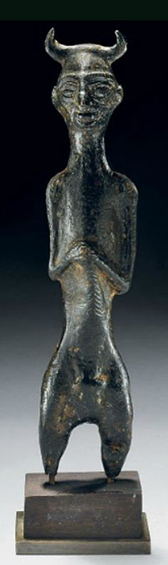 A LURISTAN BRONZE HORNED FIGURE   EARLY 1ST MILLENNIUM B.C.   The stylized elongated figure wearing horned headdress, with large heavy rimmed eyes under long incised eyebrows, large nose and fleshy lips, hands clasped in front holding a sword(?), faint traces of an incised belt, prominent buttocks behind, mounted  5 in. (12.7 cm.) high