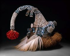 Africa |  Kuba Mukenga Mask. Democratic Republic of the Congo  Kuba peoples. Late 19th/mid-20th century.  Wood, glass beads, cowrie shells, feathers, raffia, fur, fabric, thread, and bells.  Mukenga masks like this one are worn at funerals of influential, titled men in the northern part of the Kuba kingdom. The mask's form and materials combine symbols associated with status and leadership.