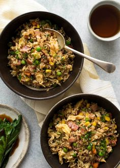 Overhead photo of two rustic dark brown bowls with Egg Fried Rice.