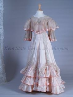 C. 1905, Pink chiffon pink cotton and lace day dress. Bodice with wide neck of lace with falling chiffon ruffle, puffed sleeves trimmed with pink satin ribbon. Skirt with 3 tiers of cotton ruffles, overskirt with inset and falling lace trim.